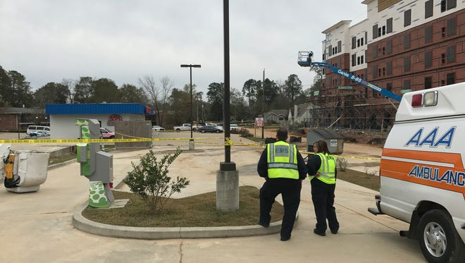 AAA Ambulance workers look at the scene at The District at Midtown where a person was killed Friday morning.