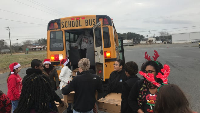 Volunteers load 200 boxes of food into a school bus for the Bank of Cheer.