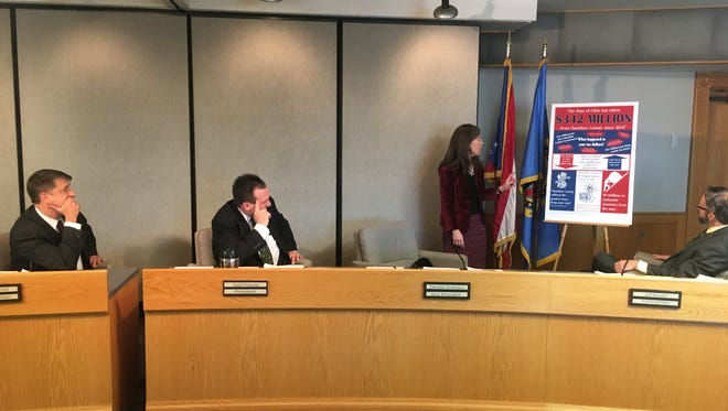 Hamilton County Commissioner Denise Driehaus gestures to a poster she made illustrating the state cuts to the county. Commissioners Chris Monzel(left) and Todd Portune look on.