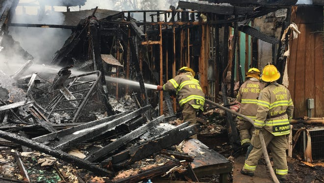 A firefighter sprays foam on a mobile home that was destroyed in a fire Wednesday in Crimora.
