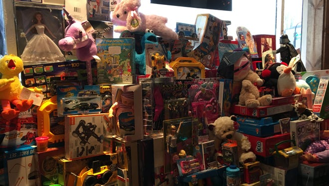 Toys are piled up inside Tommy Kirschbaum's tattoo shop MidWest Tattooers, at the front window in downtown Marshfield.