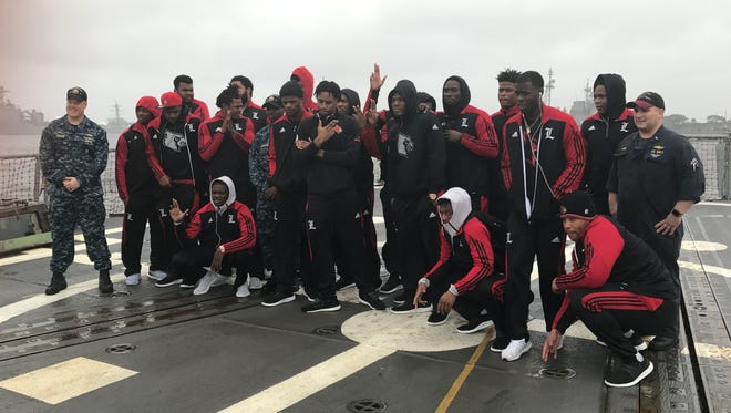 Louisville football players pose on the deck of the USS Farragut at Naval Station Mayport on a team outing Thursday in Jacksonville, Fla.