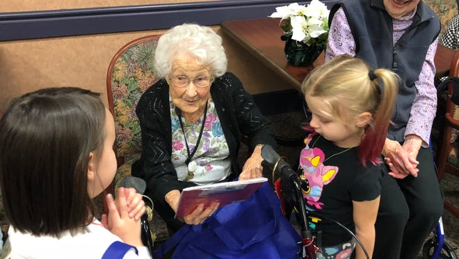 Mary Slucter, 99-year-old resident at Botsford Commons, talks to students about their new books.