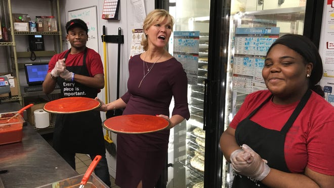 Donatos Pizza board chair Jane Grote Abell, center, stands with Murfreesboro store associates Eli Rachell, left, and Joy Daniel after the two competed for fastest pizza making.