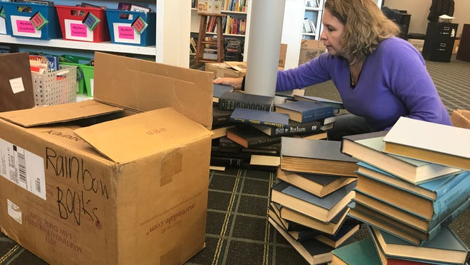Mary Kool, a volunteer at Reach Literacy, stacks books in preparation for the first day of the nonprofit's new literacy center. The center is scheduled to open Tuesday.