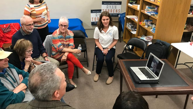 A group of Escambia County Democrats listen to former Miami Beach Mayor Phillip Levine speak over FaceTime on a MacBook at the party's local office in Pensacola on Wednesday, Jan. 10, 2018.