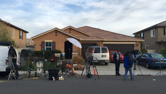 News reporters gather at the Perris home where two parents were arrested after Riverside County sheriff deputies found their many children chained to beds, locked up and malnourished in a dark, foul-smelling home.
