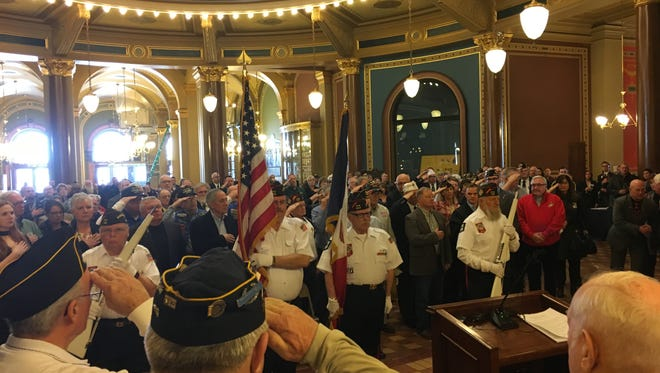 Veterans salute at the Iowa Capitol rotunda as the American and Iowa flags are presented Jan. 17 during a veterans program.