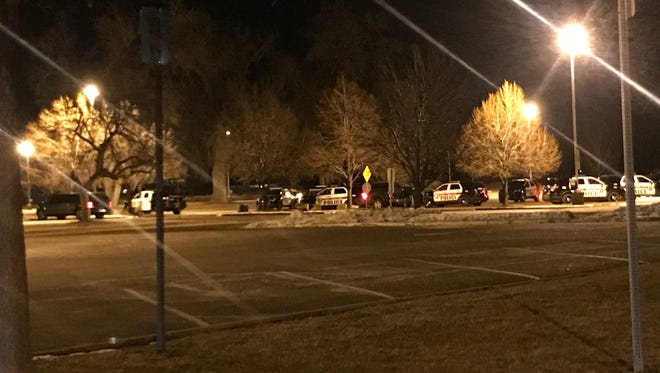 Police cars gather in the parking lot of Rocky Mountain High School Thursday night after a report of a hostage situation nearby.
