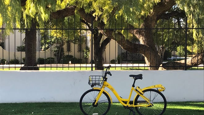 An ofo ride-sharing bike is seen parked outside of a house  in Phoenix's Arcadia neighborhood on Jan. 19, 2018.