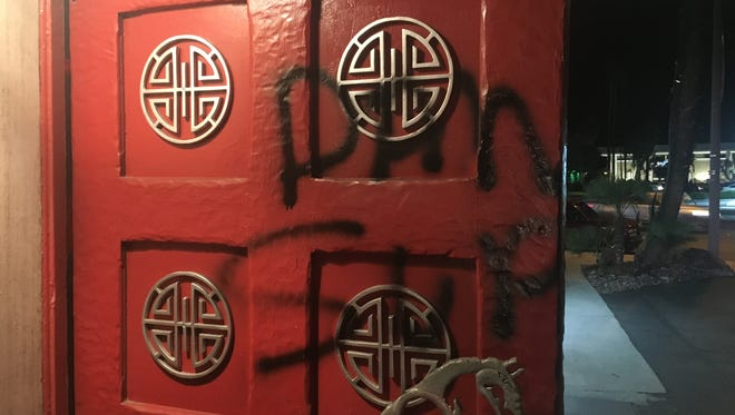 The left entry door at Wang's in the Desert with part of a spray painted message.