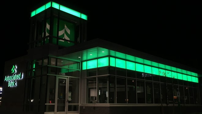 Green Bay-based Associated Banc-Corp said Friday it would close 14 bank branches and open one new branch as the shift toward digital banking among consumers continues.