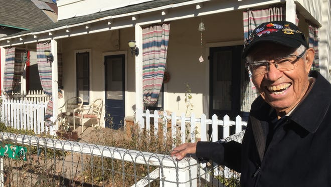Angel Delgadillo stands outside his childhood home in Seligman.