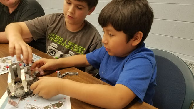Joshua Gelona of Bridgeton works with Jesus Luna of Hopewell Crest to build a working robot during a program at Cumberland County Library in Bridgeton.