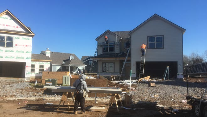 Construction workers build a home in the Enclave at Berkshire subdivision.