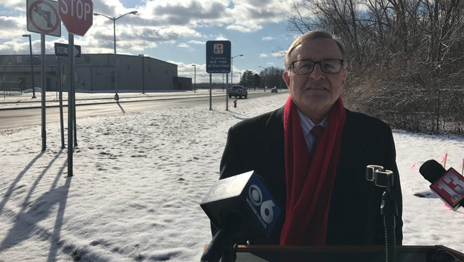 """Republican gubernatorial candidate John DeFrancisco speaks near Albany International Airport on Monday, Feb. 5, 2018, in front of controversial """"I Love NY"""" road signs."""