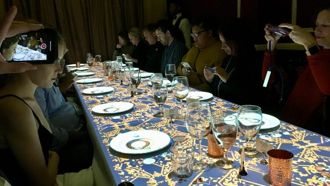 Nashville reporters take pics and videos of animated images on their plates at Dinner Time Stories show at The Standard restaurant downtown Jan. 31