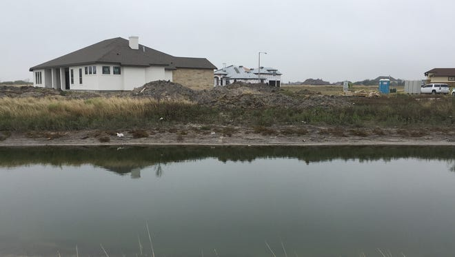Construction of homes continues along Oso Creek — some close enough that their roofs are reflected in the water. The city is expected to soon have new flood maps, the first substantial updates since maps were issued in 1985.