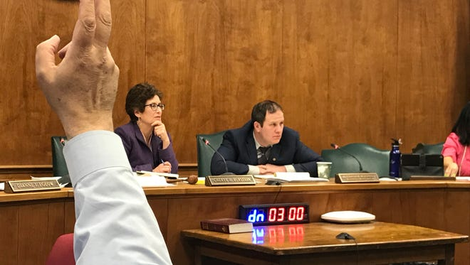 A Millburn resident raises his hand to speak during the Township Committee's Tuesday, Feb. 7, 2018 meeting where plans for controversial development on Chatham Road were discussed. Mayor Cheryl Burstein, left, at Township Administrator Alex McDonald are at the dais, while a timer shows the three minutes available to each member of the public addressing the governing body.
