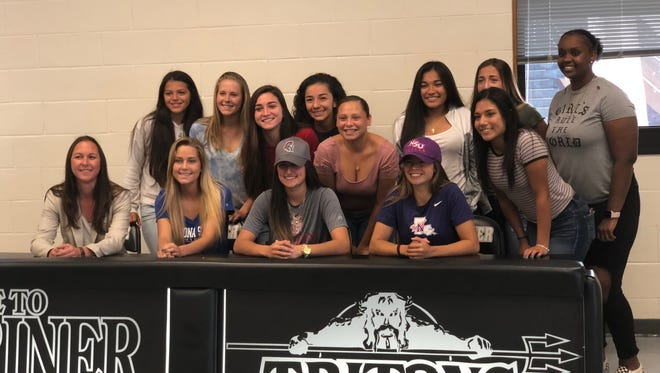 Cassidee Rentsch, Acelya Aydogmus and Karleigh Acosta are joined by their Mariner soccer teammates after signing with Daytona State, Troy and Northwestern State, respectively, in a ceremony at the school.