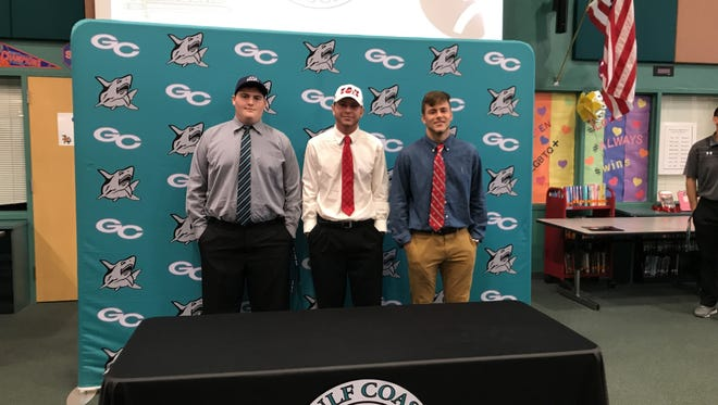 Gulf Coast football players Randall Taylor (left), Kaden Frost (center) and Christian Wagner (right) pose after signing their letters of intent during a ceremony at Gulf Coast High School on Wednesday afternoon.