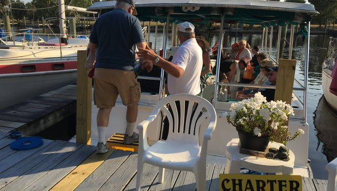 Capt. Bob Beckstrom helps a passenger board his boat for a sunset cruise from Marinatown in North Fort Myers.