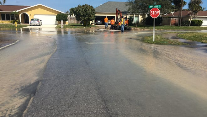 Crews work to repair a water main break at Bay Drive and East Burns Boulevard in Indian Harbour Beach on Sunday
