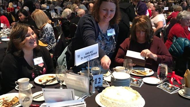 Justine Perovich cuts a birthday cake as Victoria Record looks on at the annual Susan B. Anthony Birthday Luncheon on Feb. 14, 2018.