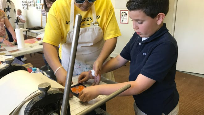 Kash Kupfer, 8, gets some help from artist Salle Kirby in making a greeting card with a dinosaur during Art for Kids Day at Desert Art Center in Palm Springs on Saturday, Feb. 10,2018. This year, Desert Art Center is offering its first summer camp art classes for middle school-age kids -- for free.