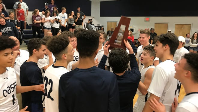 The Oasis boys basketball team lifts its District 5A-10 boys basketball trophy after beating Community School of Naples Friday.