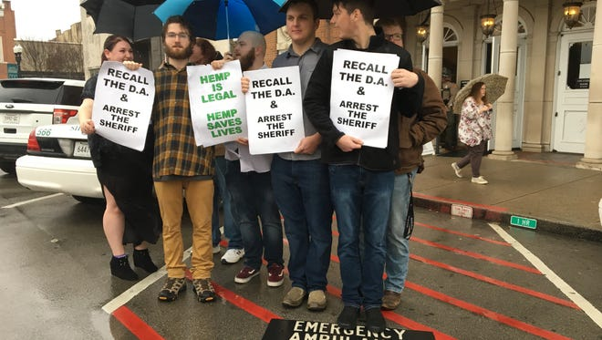 A heavy downpour fell on a group gathered at the Rutherford County Judicial Building Friday in support of shop owners accused of selling CBD oil, a nonpsychoactive product often used to help treat pain. Holding water-logged signs are, from left, Julia Beasley, Luke Sabin, Christian Powers, Logal Weaver and Tyler Bailey.