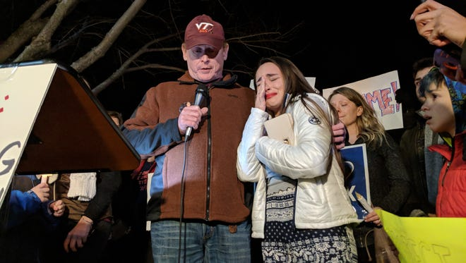 At a gathering outside the National Rifle Association's headquarters in Fairfax, Virginia, Gillian Beard cries as she is held by speaker Peter Reed, whose daughter was killed during the 2007 Virginia Tech shootings.
