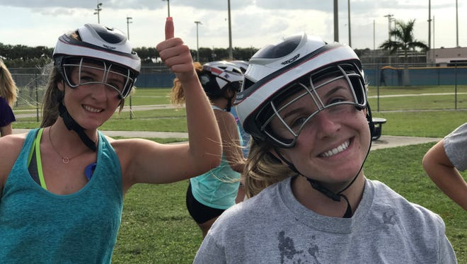 Estero lacrosse players Gracie Cory (left) and Sophie Forker show off their new helmets. FHSAA girls lacrosse teams are required to wear the helmets for the first time in 2018.