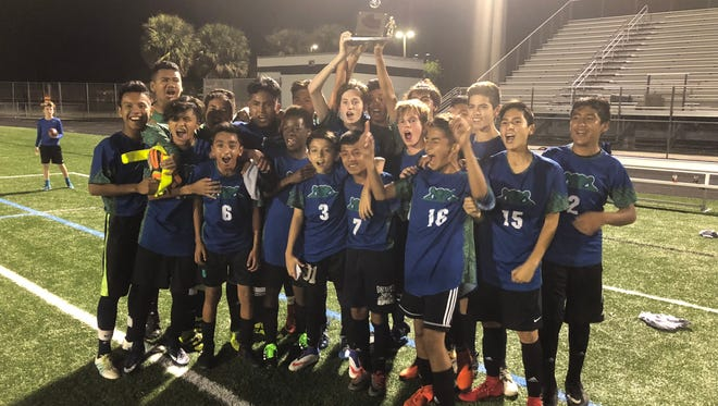 The East Naples Middle School boys soccer squad celebrates winning the Collier County championship after a 4-1 win over Pine Ridge on Friday, Feb. 23 at Gulf Coast High School.