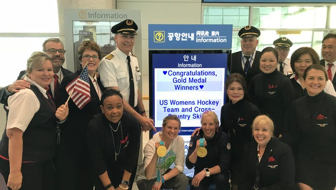 Team USA cross-country skiers Jessie Diggins (left) and Kikkan Randall hold up their gold medals as they pose for a photograph with the pilots and crew of a flight before departing from Seoul, South Korea. The pair won the United States' first ever gold medal in the event at the 2018 Winter Olympics.
