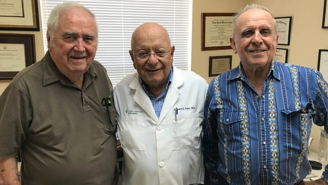 From left, Bernie Malone, Howard E. Voss, MD, Pat Bradley pose for a photo at the VIM Clinic facility.