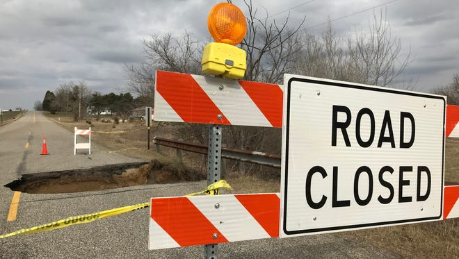 A large sinkhole, at least 11 feet wide and eight feet deep, is the result of recent flooding and an aging drainage structure beneath North Cochran Road, officials said.