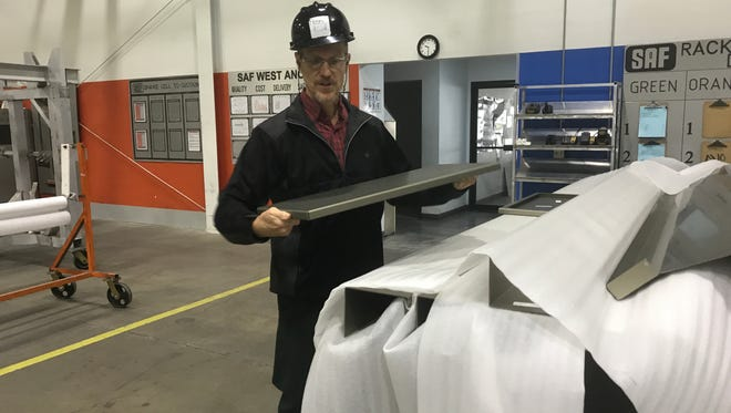 Penn McClatchey, CEO of SAF, holds up a finished piece of aluminum inside his Redding plant. McClatchey believes an aluminum tariff will force his company to raise their costs.