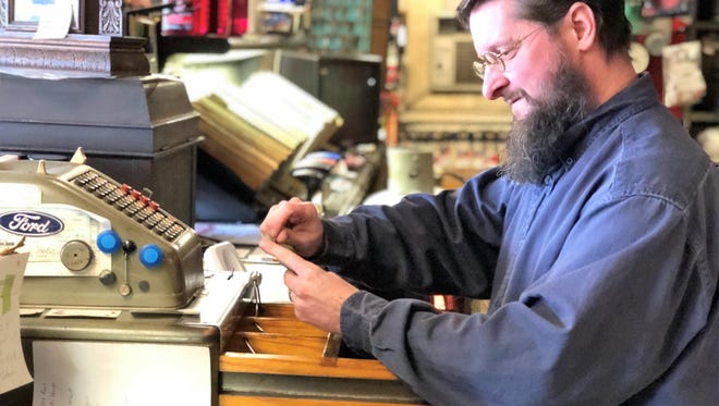 Roger Berry rings up customers on a vintage cash register. They had an electric one but when they were cleaning it, it fried and they have been using this vintage one for as long as they can remember.
