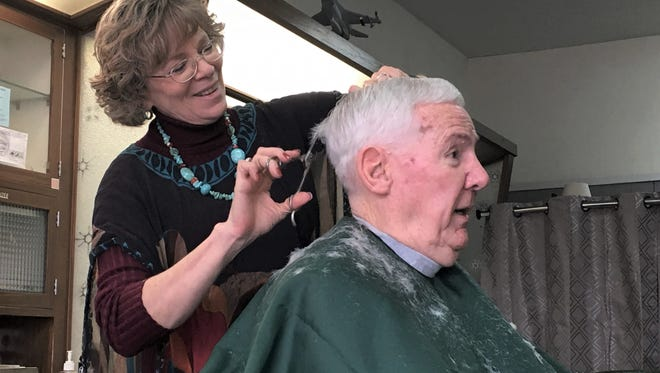Barber Anne Douglas cuts Lewis Wingert's hair at Southway Barber Shop on Wednesday. Douglas recently purchased the shop from its long-time owner, Larry Ramharter.