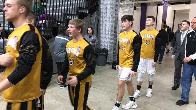 The Lebanon High School boys' basketball team wears commemorative ribbons to honor three community members lost over the last week as they walk into the Class 3A regional final game in Greencastle on Saturday, March 10.