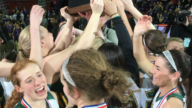 The Beaver Dam girls basketball team celebrates its Division 2 championship after defeating New Berlin Eisenhower 51-41 on Saturday evening at the Resch Center in Ashwaubenon.