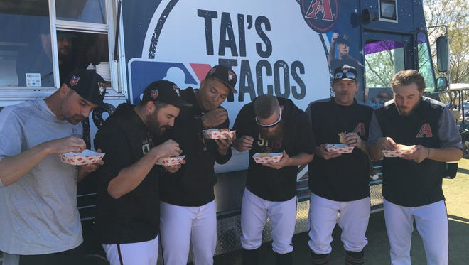 Diamondbacks players bite into tacos made by pitcher Taijuan Walker. The players showed up to his taco truck in a golf cart ahead of their game against the Colorado Rockies at Salt River Fields on Tuesday.