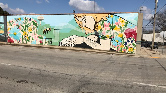 """A mural of flowers, honeybees and a child reading a book that the city of West Allis had done to help beautify the city was vandalized by someone who spray-painted the word """"kings"""" on the girl's arm."""