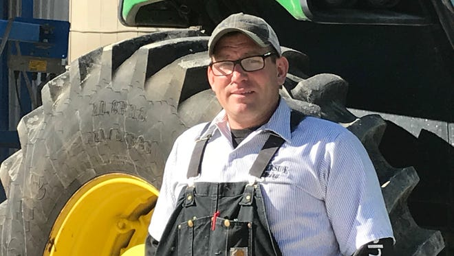 Andy Fisher stands with a tractor he uses on his Reedsville farm.