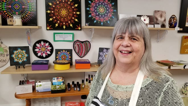 Barb McWithey, owner of Macy Place, stands near some of the artwork taught at the many classes held in her business.