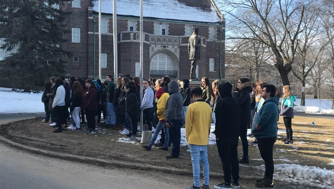 """Manitowoc Lincoln High School students gather around the statue of Abraham Lincoln outside the school during their National Walkout Day demonstration, titled """"Remembering the 17."""" The demonstration memorialized the 17 people who died during a Feb. 14 shooting at Marjory Stoneman Douglas High School in Parkland, Florida."""