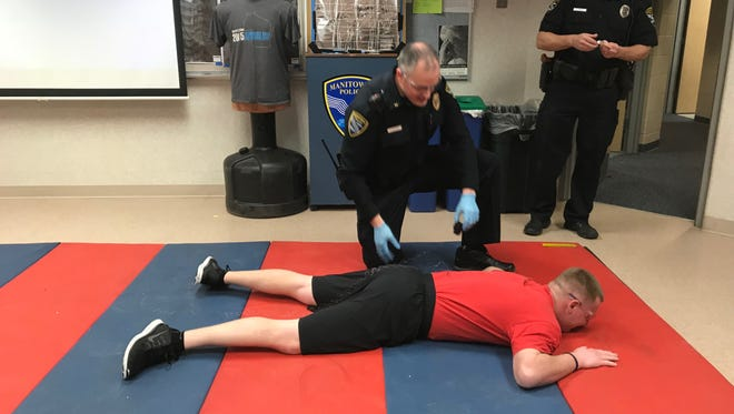 Manitowoc Police Officer Austin Schleis lies on the ground after being tased while Officer Paul Behrendt takes the probes out of Schleis' back.