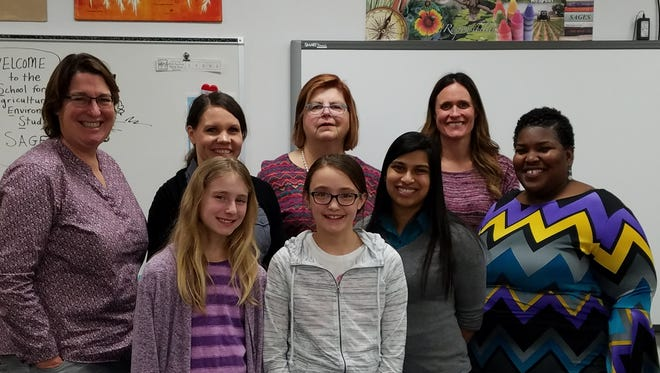 "The staff and students of SAGES Charter School, Fox Lake were proud to host Alpha Xi educators and shared with them their achievement of a ""Significantly Exceeds Expectations"" rating from the Department of Public Instruction. Pictured, back row, from left are: teachers Beth Plier, Sheri Hicken, Linda Evans,and Erin Fitch; front row: students Naomi Kelly and Olivia Fitch, Principal Jewel Mucklin, and teacher NaQuisha Mann."