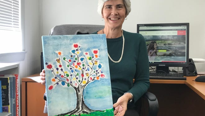 Autism Pensacola President and CEO Susan Byram shows off a painting on Wednesday, March 21, 2018, that children at the Autism Pensacola camp helped create.